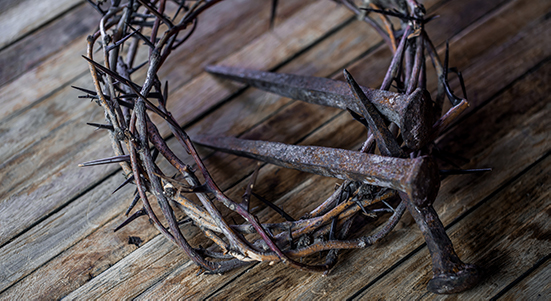 Crown of thorns with blood dripping, nails on stone. Christian concept of Jesus Christ suffering